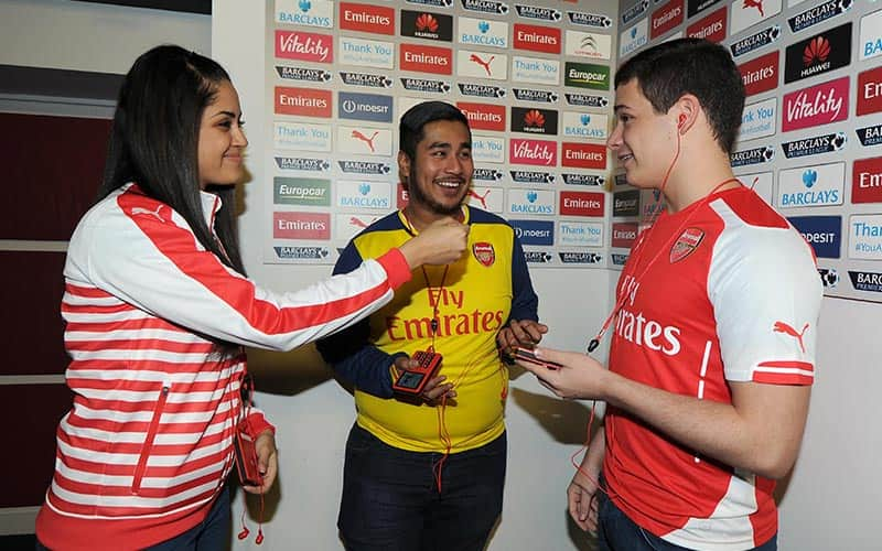 A woman pretending to interview two men in Arsenal tops in the Arsenal press room