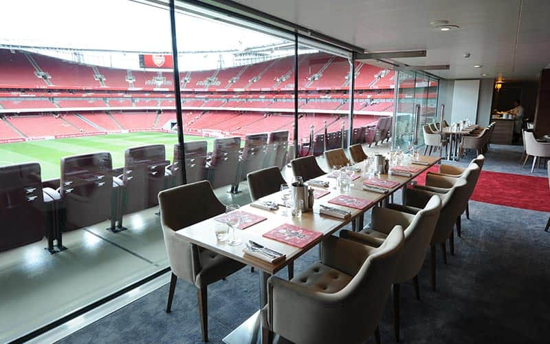 A long table set for dinner in the Emirates restaurant, with the pitch and seating in the background