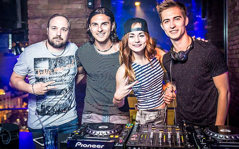 Four people behind the DJ decks, posing for a photo