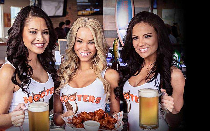 Three members of staff from Hooters holding pints and food