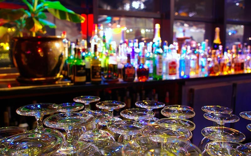 A fully stocked bar with glasses in the foreground