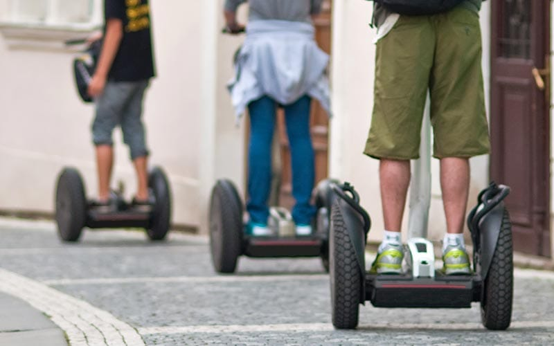 The legs of three people riding segways on the pavement