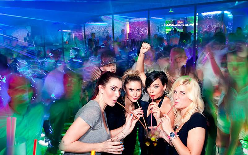 Four women posing in a club, with blurred people dancing in the background to a backdrop of green and blue light