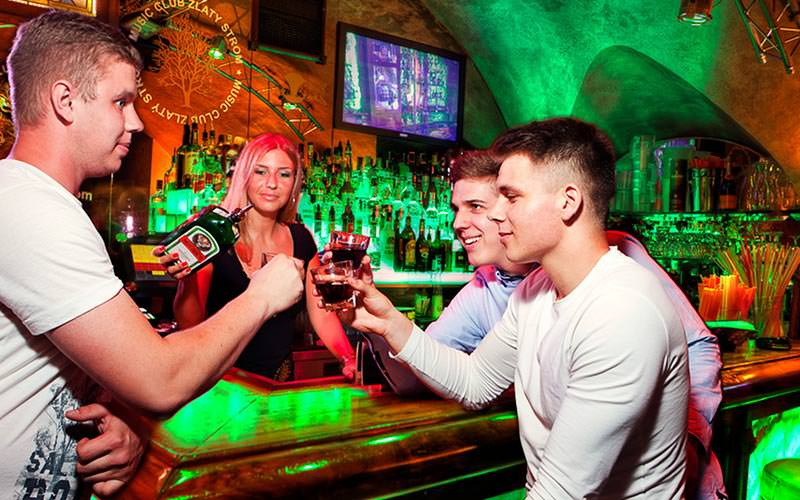 A female bartender pouring Jagermeister out for three men in front of the bar