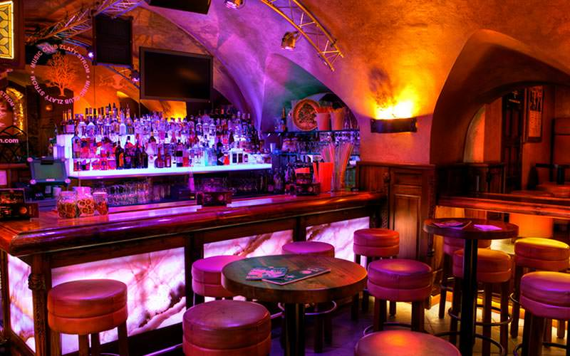 An underground bar, with tables and chairs in front and an arched ceiling, to a backdrop of purple light