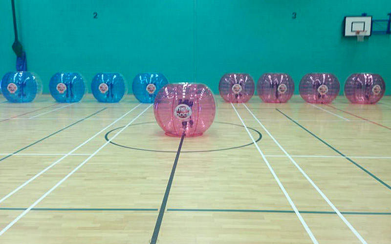 Eight inflated zorbs laid out in a line in a leisure centre, with one pink zorb in the foreground