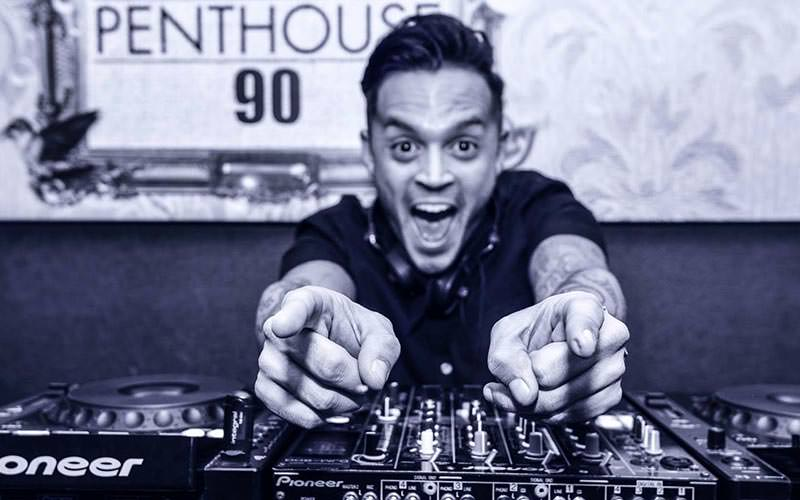 Black and white image of DJ in a DJ booth, pointing and laughing