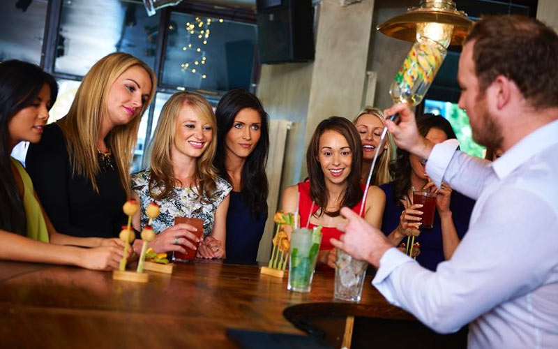 A bartender making a cocktail with a group of women watching