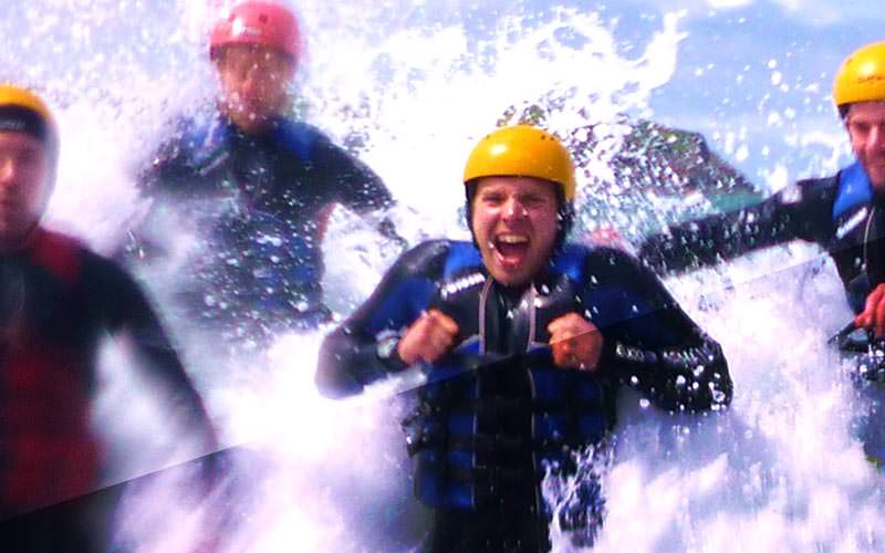 A man in a life jacket being splashed by the river, with blurred people in the background