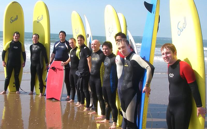 People standing on the beach with their surfboards
