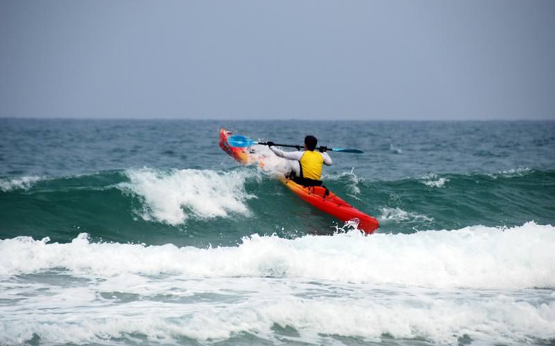 The back of a man riding a wave in the sea, on a kayak