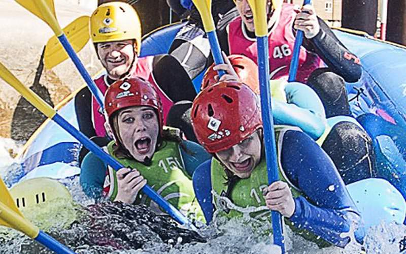 Some people screaming whilst white water rafting