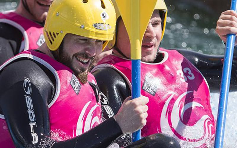 Some men wearing pink vests, rowing a white water raft