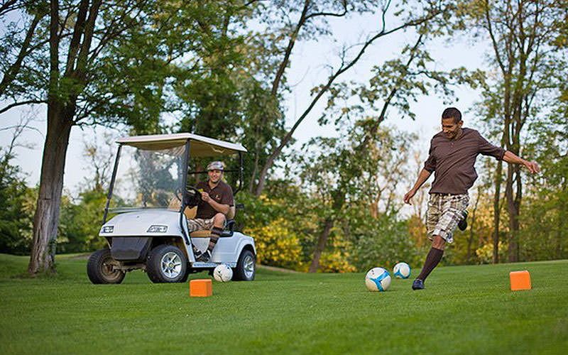 A man in golf attire kicking a football on a golfing green, with a man sat in a golf kart in the background