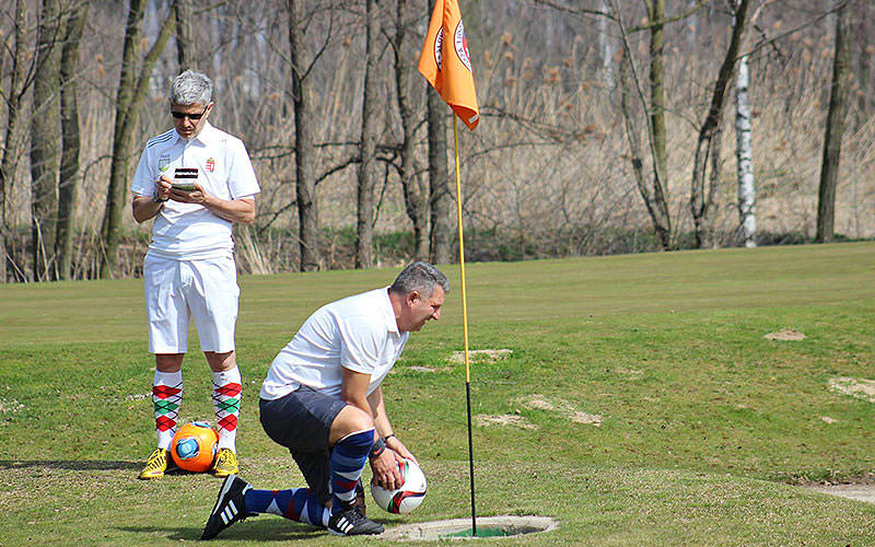 A man crouching down at a footgolf hole on a course, with a man writing on a pad in the background