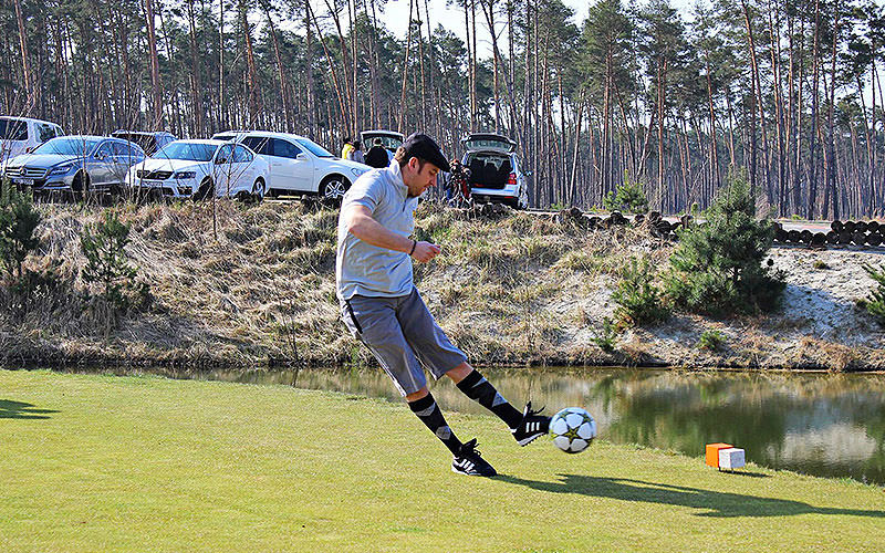 A man in golf attire kicking a football on a golfing green
