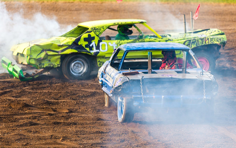 Two cars crashing into each other while smoke fills the air