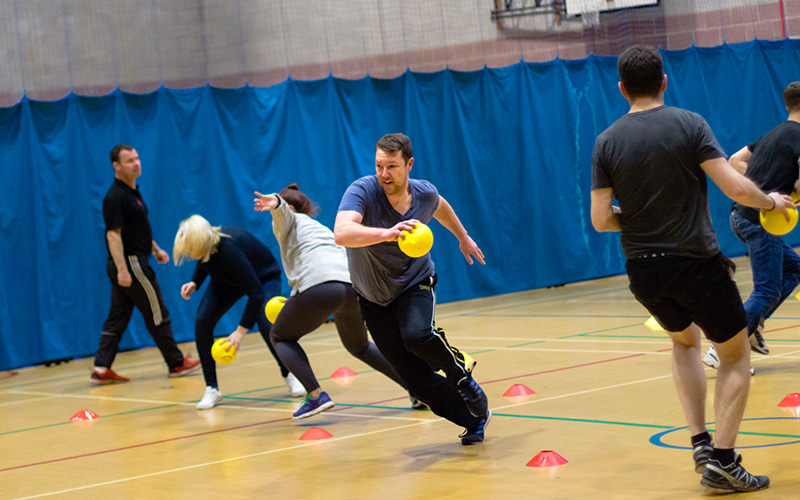 Several people running with dodgeballs in their hand