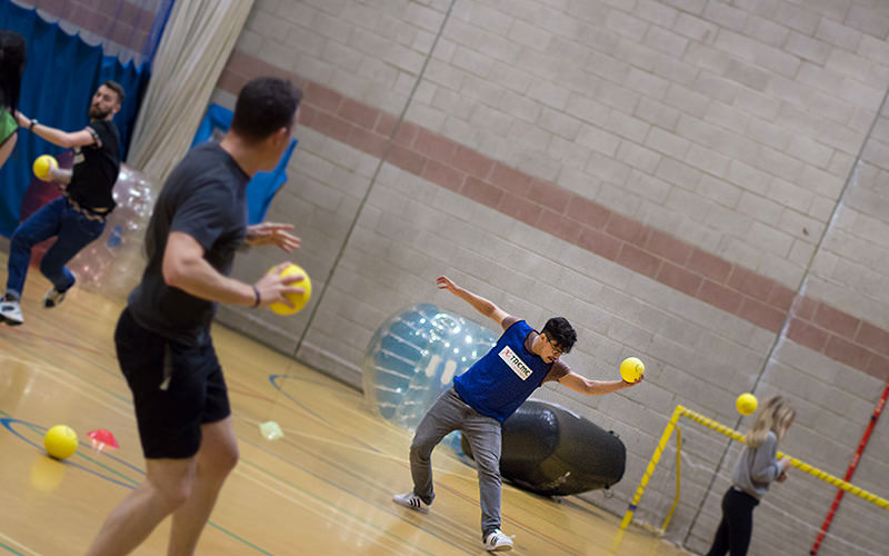 A man catching a dodgeball in mid-air