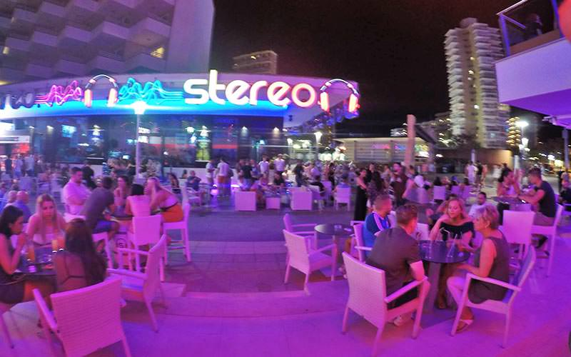 People sat outside on seats, at night, in front of Stereo