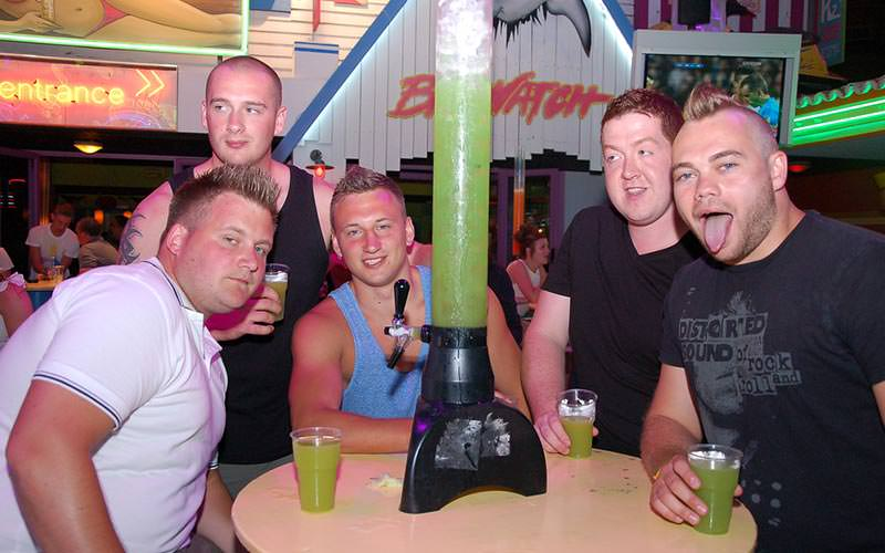 Five lads with drinks, sitting outside Baywatch bar in Magaluf