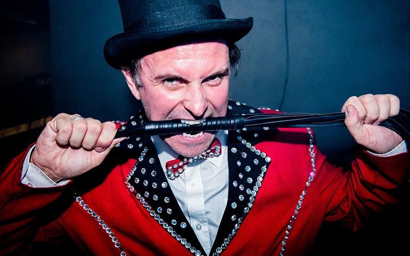 A circus ringleader biting a pole