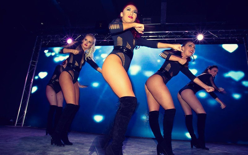 Five girls wearing over the knee boots and black bodies, dancing on stage