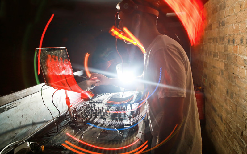 A man DJing and a bright light in the background