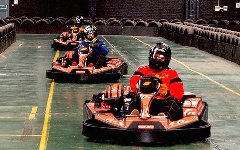 Three go karts racing down the home straight towards the camera.