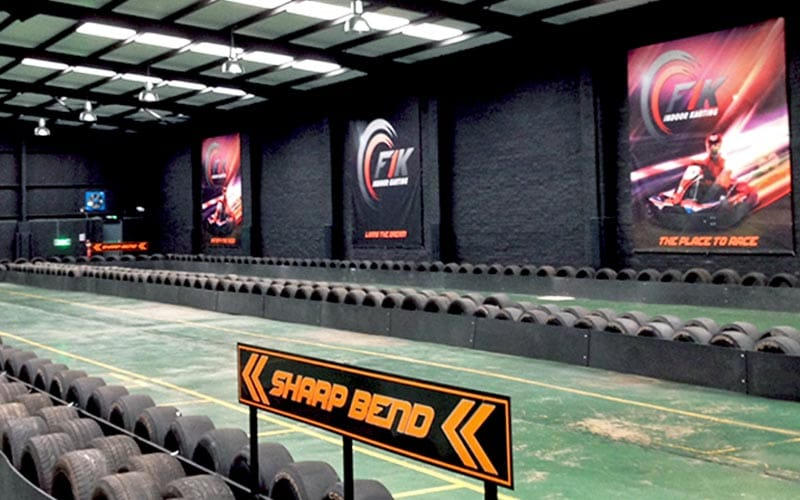 Sharp bend ahead sign in front of the track,with logo and go kart images on the wall.