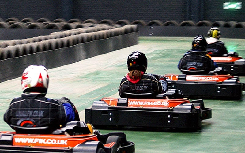 Four go karts racing away from the camera down the home straight.