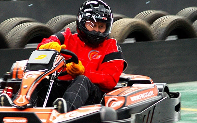 Close up of go karter wearing a red jumpsuit with tyre wall in the background.