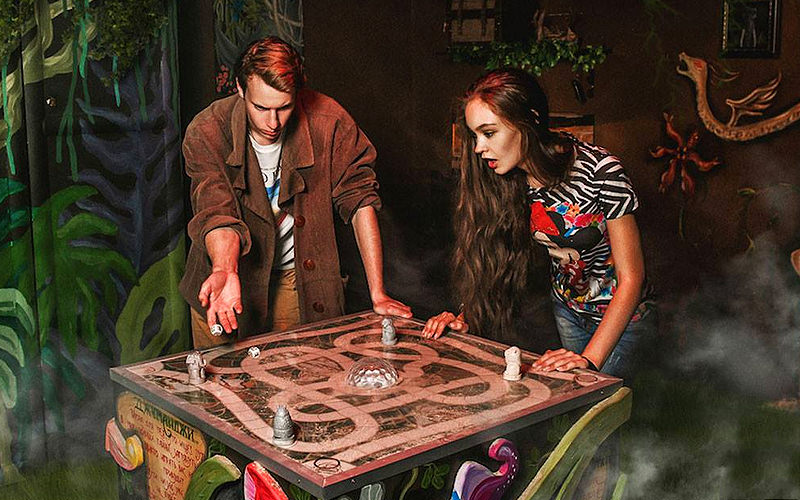 A man and a woman in an escape maze looking at a board game while rolling two die