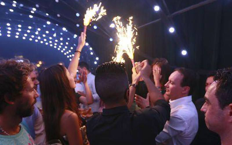 Some men and women holding sparklers in a nightclub