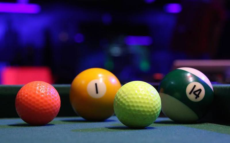 Two golf balls and two snooker balls on a table