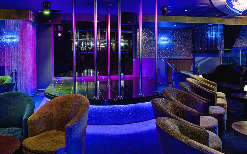 Seating in front of the pole dancing stage at For Your Eyes Only Southampton, to a backdrop of purple and blue light