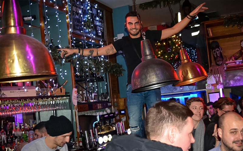 A man standing on top of a bar