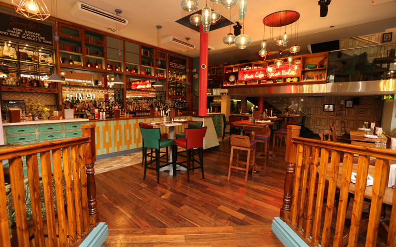 A large room with several small tables and chairs and a large bar