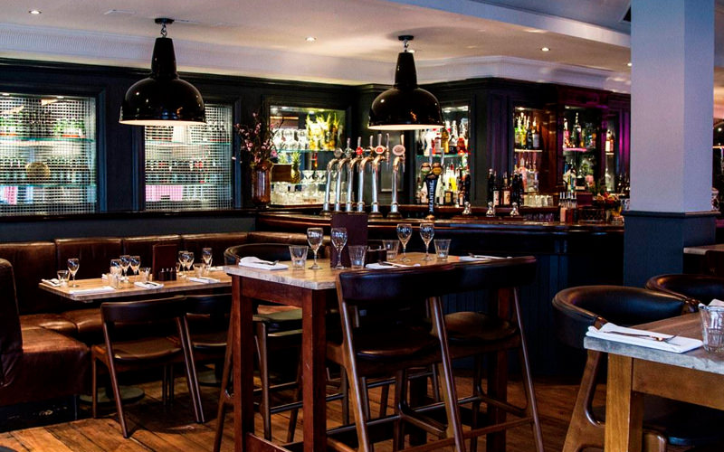 A view of a bar with several tables and hanging lights