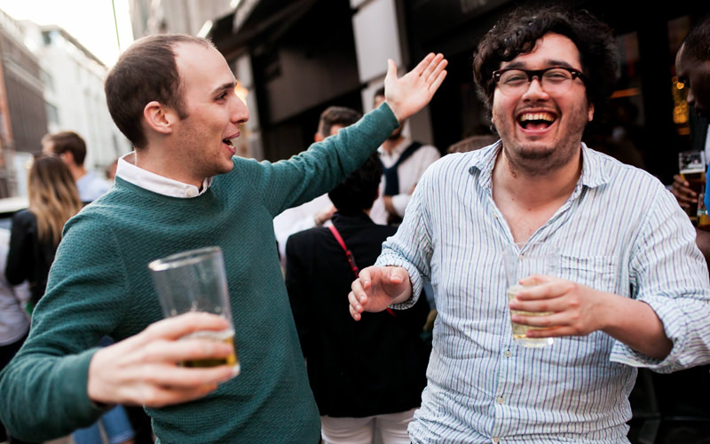 Two men laughing outside of The Warwick