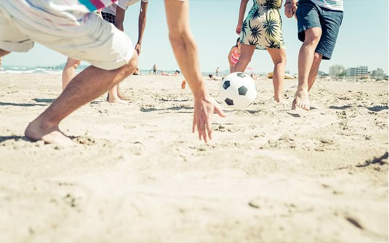 Close up of men's legs playing football on the beach