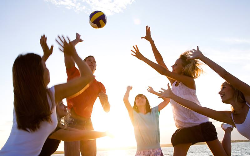 A man and five woman reaching up for a volleyball on the beach