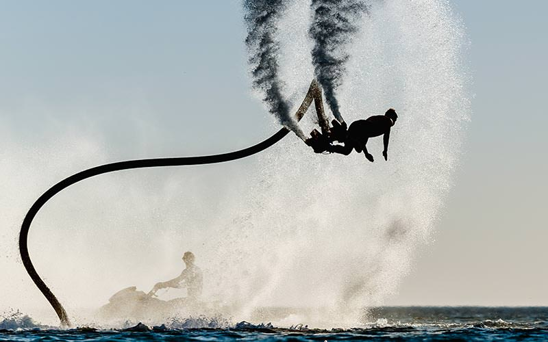 An image of a man flyboarding in the air