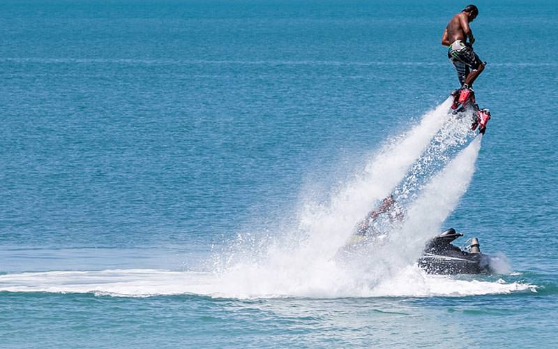 A man flyboarding in the sea, with a jet ski in the back
