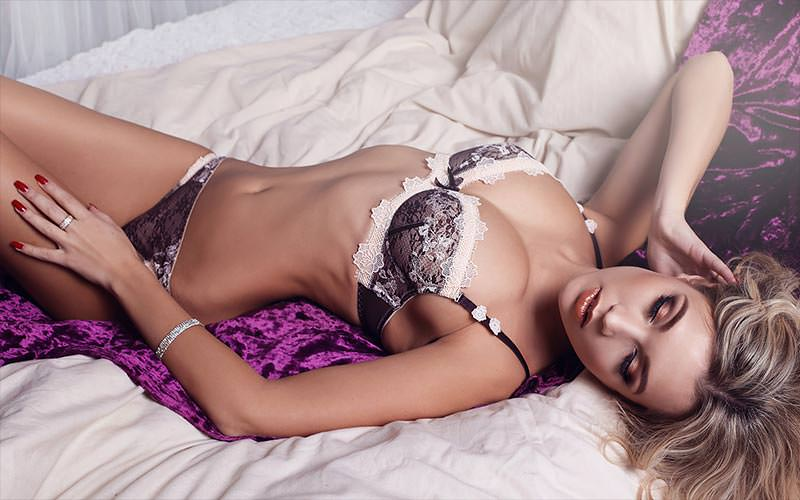 A blonde girl wearing just her underwear, lying on a bed