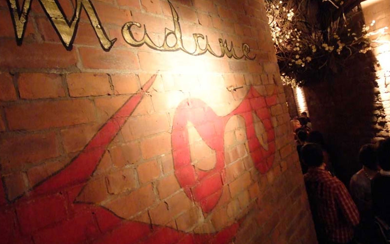 Madame Koo logo on a wall inside the club