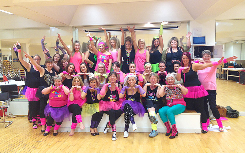A group of women in brightly coloured outfits posing during a dance class