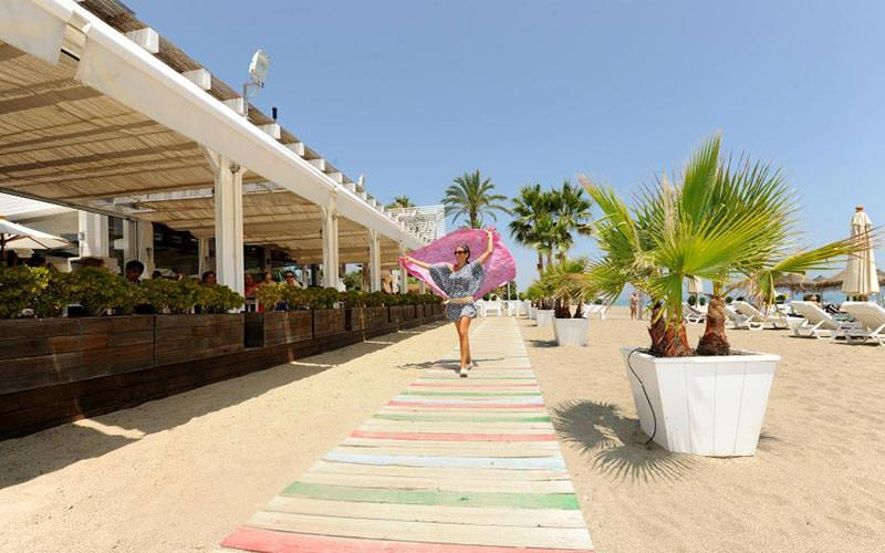 A woman walking on a path on the beach, with a restaurant on one side and sun beds on the other
