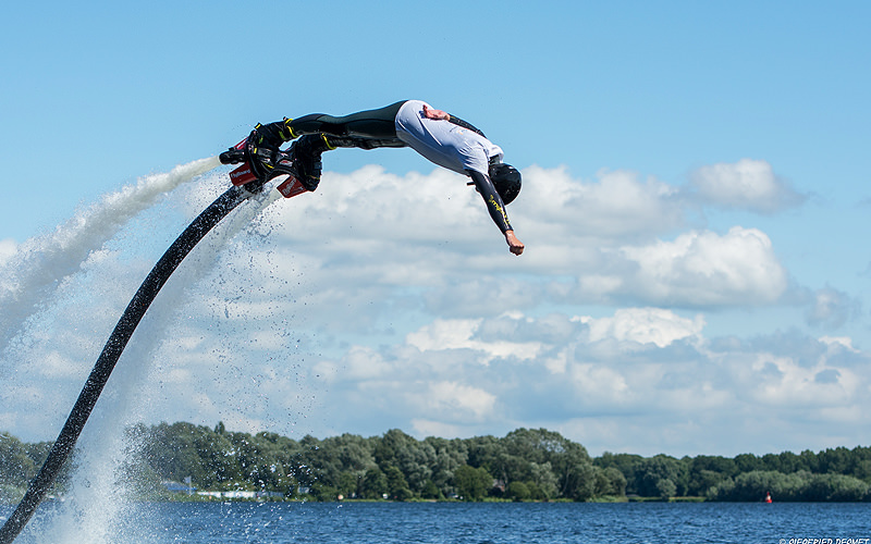 A man attached to a flyboard in mid-air
