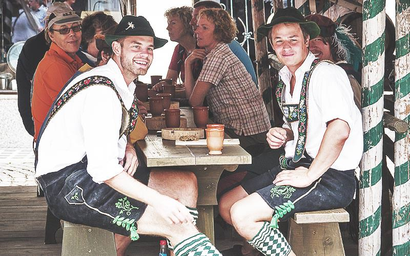 Two men in lederhosen costumes and sat at a bench, with people sat in the background